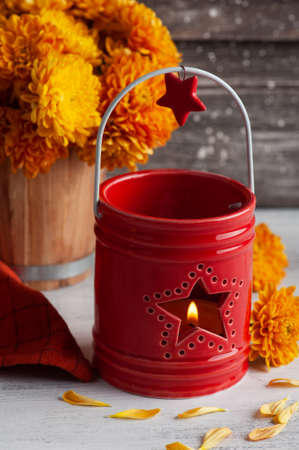 Lit aroma red candle and orange flowers on rustic background. Greeting card for celebration