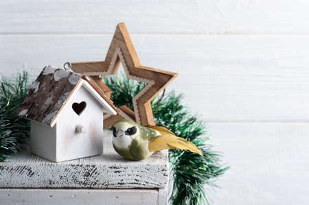 Christmas interior decoration whit birdhouse and bird on white rustic background with copy space