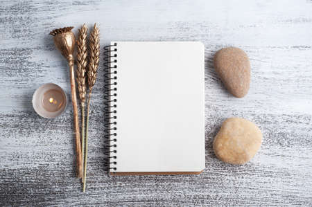 Empty open notebook and dry golden flowers on rustic background. Greeting card with copy space for your text