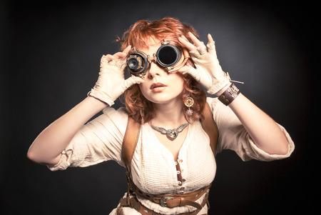 steampunk goggles: Hermosa mujer steampunk redhair mirando por encima de sus gafas