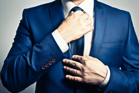 Businessman in blue suit tying the necktie