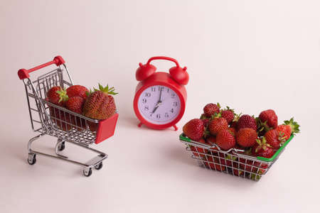Fresh red strawberry in a mini basket and a clock on a white background. Harvest time concept in the garden.