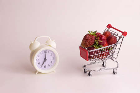 Retro clock and basket with strawberry on a white background. Harvest time concept in the garden.