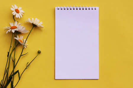 bouquet of flowers and a blank notebook on a yellow background. Top view, flat lay.