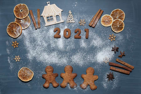 The New Year's table is decorated with gingerbread men and numbers for the New Year - 2021. Wooden decorative toys and items for baking. Christmas festive decor or postcard.
