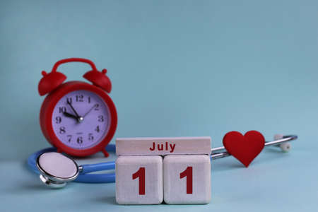 July 11. White wooden calendar blocks with date, clock and stethoscope on blue pastel background. Selective focus. health concept.