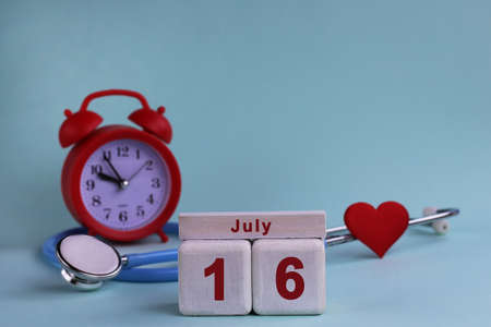 July 16. White wooden calendar blocks with date, clock and stethoscope on blue pastel background. Selective focus. health concept.