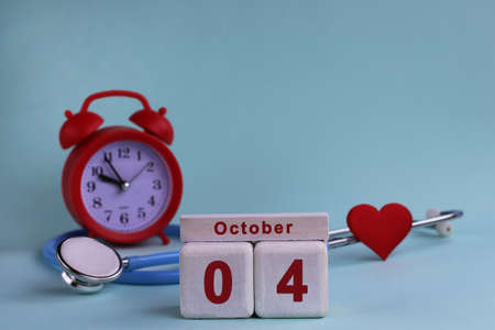 October 4. Day of the 4th month, calendar date. White wooden calendar blocks with date, clock and stethoscope on blue pastel background. Selective focus. health concept Stock Photo