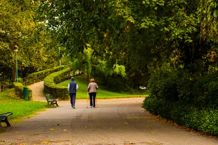 A pair of elderly people make an active morning walk in the park.