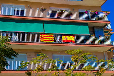 The national flag of Spain and the flag of Catalonia are hung out together on the balcony of the building in Catalonia as a symbol of friendship and unity of the province and the state of Spain. Stock Photo