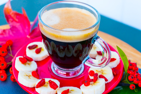 Transparent cup of coffee with foam on a red saucer with pieces of banana and goji berries.