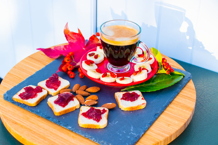 A cup of coffee, bread with confiture, almonds, banana, berries on the outside give a shadow in the rays of the dawn.