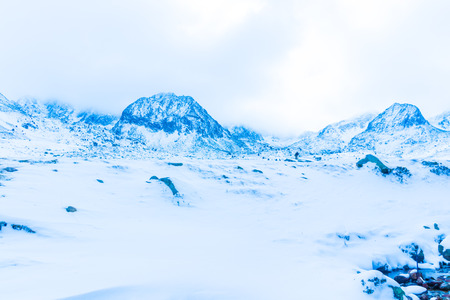 Landscape in the snow-capped mountains in foggy weather Stock Photo