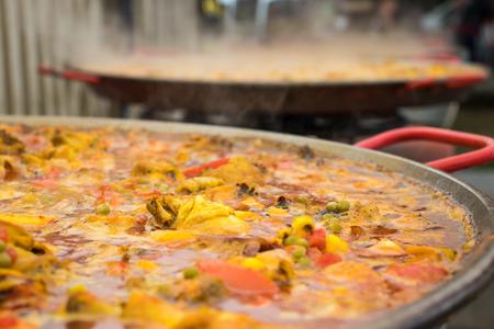 Paella in een enorme koekenpan. Het kookproces.