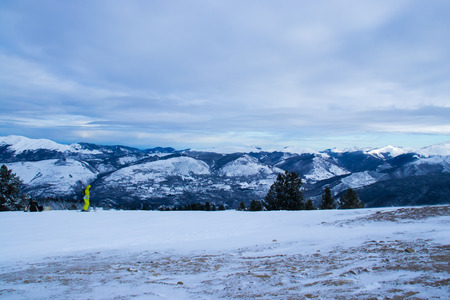 Beautiful view of the tops of the snow-capped mountains. Two skiers are preparing to descend.