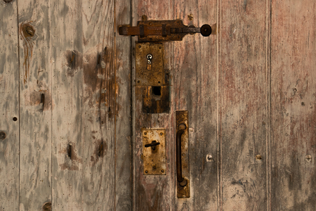 An old wooden door with a rusty bolt.