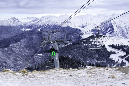 A lone skier climbs the mountains on a cable car for descent.Ski station in the mountains. There is a cable car for skiers. The tops of the snow-capped mountains can be seen. Stock Photo