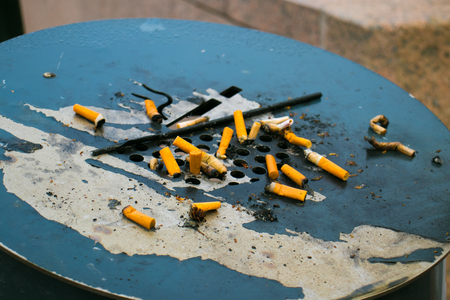Large ashtrays in a public place installed on the street full of cigarette butts.
