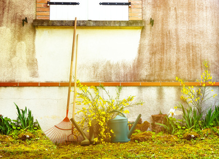 The garden tools are leaning against the wall of the house outdoors.