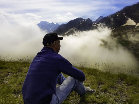 A pensive, lonely middle-aged man sits on the ground in a mountain silence against the background of clouds.