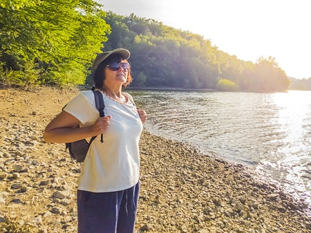 Happy elderly woman travels with a backpack and admires nature.