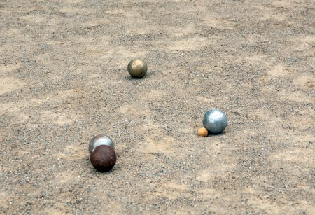 Balls of petanque on the sand during the game in the parc.