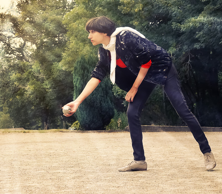 Woman throwing a petanque ball outdoor in th park on holidays Stock Photo