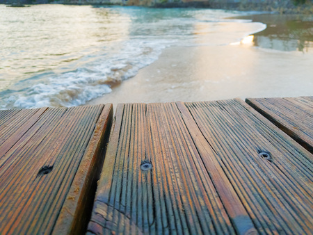 Wet wooden floorboards on the beach in the sea.
