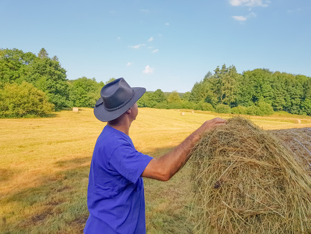 A farmer in a hat looking in the field with stacks of fresh hay after harvesting wheat .
