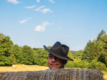 Portrait of a farmer in a hat behind a haystack in the field.