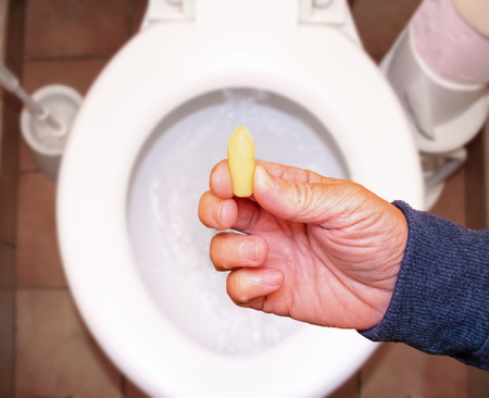 Suppository for constipation in the hand of an elderly person in the toilet against the background of the toilet bowl. 스톡 콘텐츠