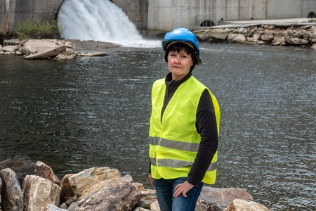 Woman in a helmet against the backdrop of hydroelectric turbines
