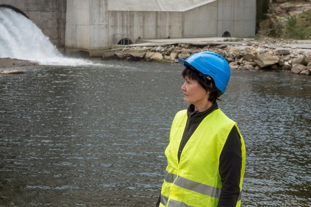 Dam and turbines of a hydroelectric power station with falling water flows and woman worker Фото со стока