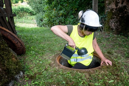 Sewer repair works in the manhole by a woman worker