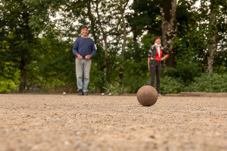Couple man and woman play petanque on fine stone field Stock Photo