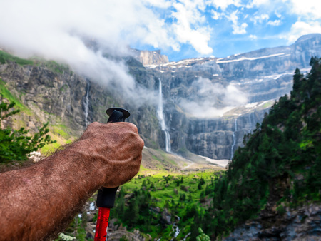 The hand of a tourist making a hike in the mountains against the background of a beautiful landscape with a waterfall. 写真素材