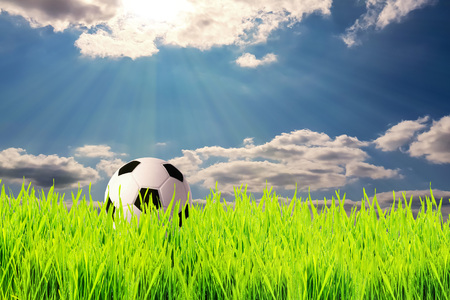Soccer ball on the green grass of a football field under the sky with clouds in the rays of the sun. Focus selectiv. 写真素材