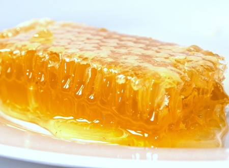 Sweet honeycomb with honey on white background, bee products, organic concept
