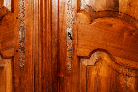 Front of the door of an old wooden cabinet with a key