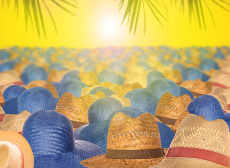 The tops of straw hats to protect from the scorching rays of the sun on a yellow background. The concept of salvation from the heat, preparing for a travel, vacation by the sea.
