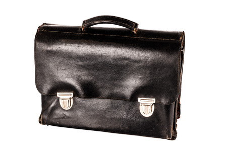 An old worn black leather briefcase closed with latches isolated on white background. Stock Photo