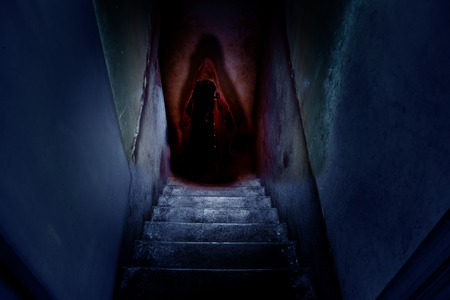 Dark figure in a red cape with a hood on the old concrete stairs in the descent to the basement. Horror movie concept.
