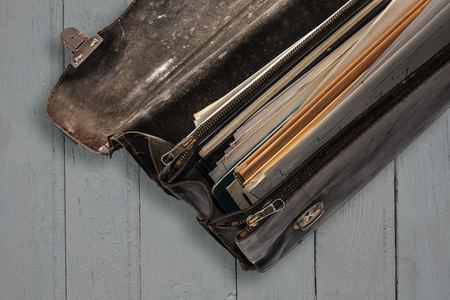 Part of old worn black leather briefcase open with papers on wooden background. Top view. Vintage style.