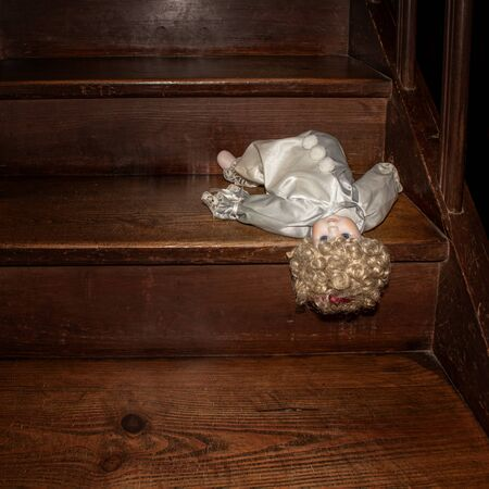 A beautiful abandoned doll in the clothes of a clown lies thrown headlong down on a wooden staircase.