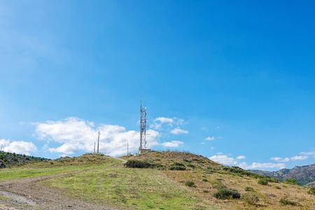 Telecommunication tower with mounted antennas on a hill with road