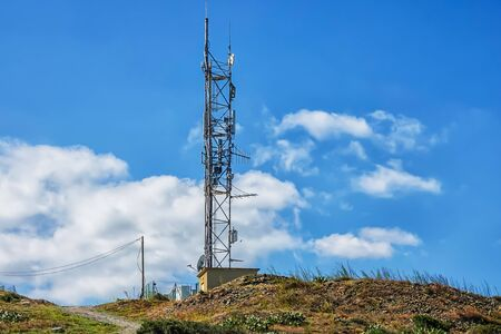 Telecommunication tower with mounted antennas on a hill