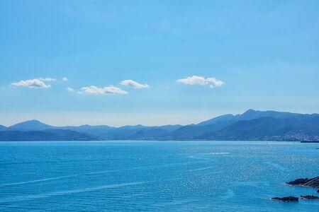 Seascape with mountain shore on the horizon on a sunny day Stockfoto