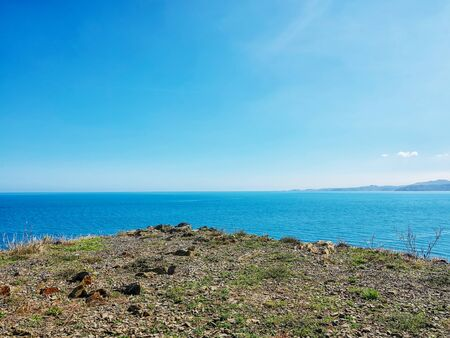 The edge of the rocky shore overlooking the endless horizon in the sea.