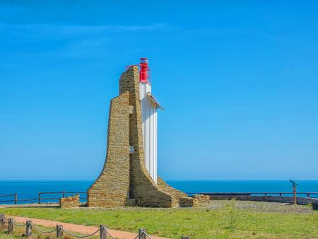Modern stone lighthouse by the sea with blue sky background