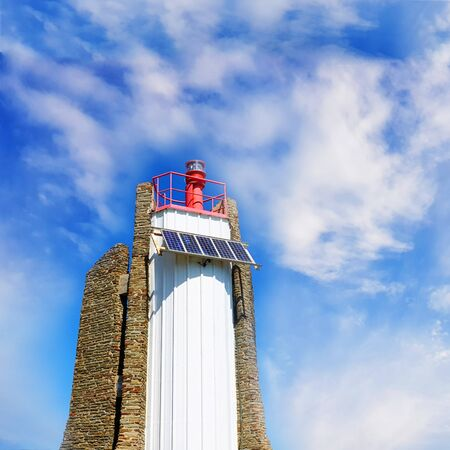 Modern stone lighthouse by the sea with blue cloudy sky background